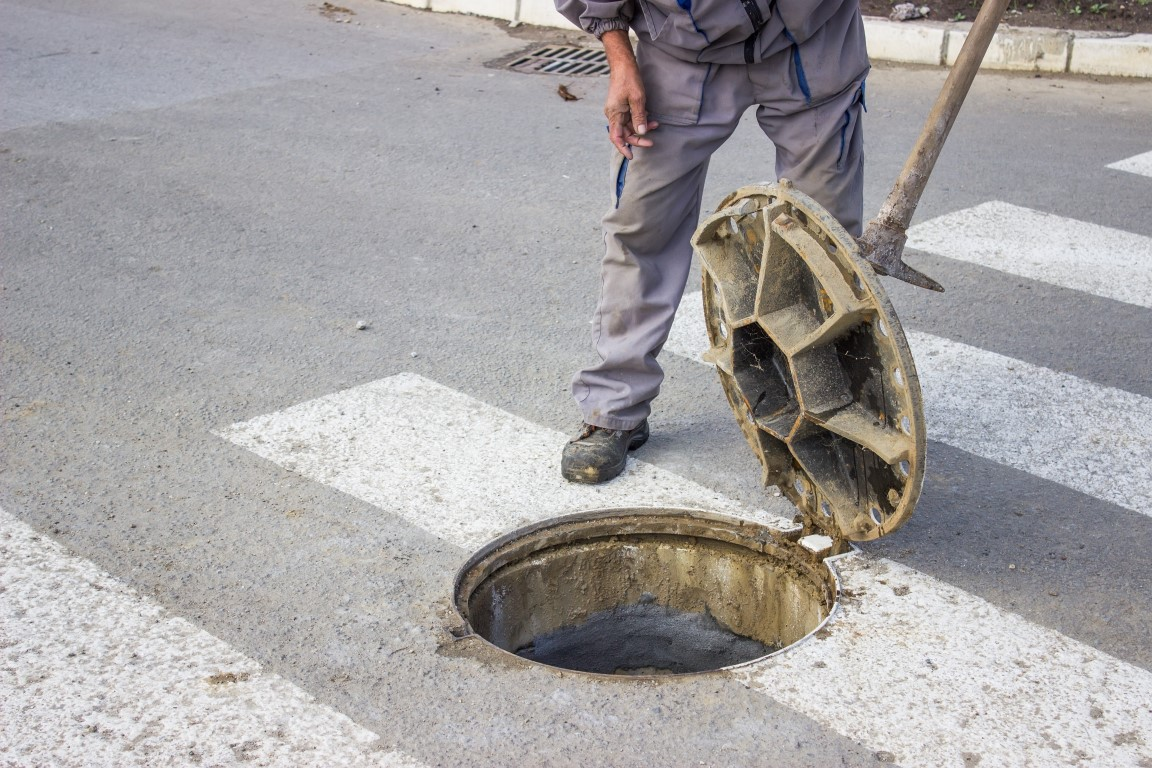 utilities worker moves the manhole cover to check the sewer line for clogs